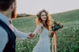 Beautiful young bride and groom outside in green nature at romantic sunset, holding hands.