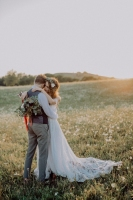 Beautiful young bride and groom hugging outside in green nature at romantic sunset.