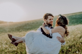 Beautiful young bride and groom outside in green nature at romantic sunset. Groom carrying bride in his arms.