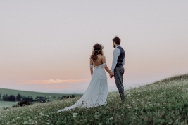 Beautiful young bride and groom outside in green nature at romantic sunset, holding hands. Rear view.