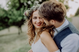 Beautiful young couple, groom and bride with flower wreath outside in green nature.